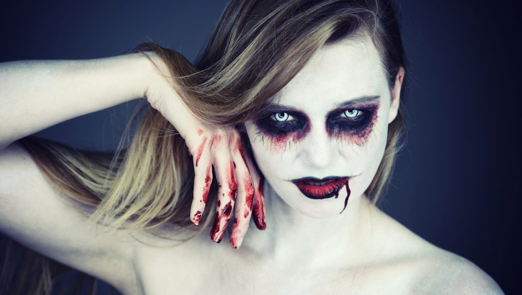 Close-up image with Halloween makeup, dark eyes and blood dripping from mouth - ACSM