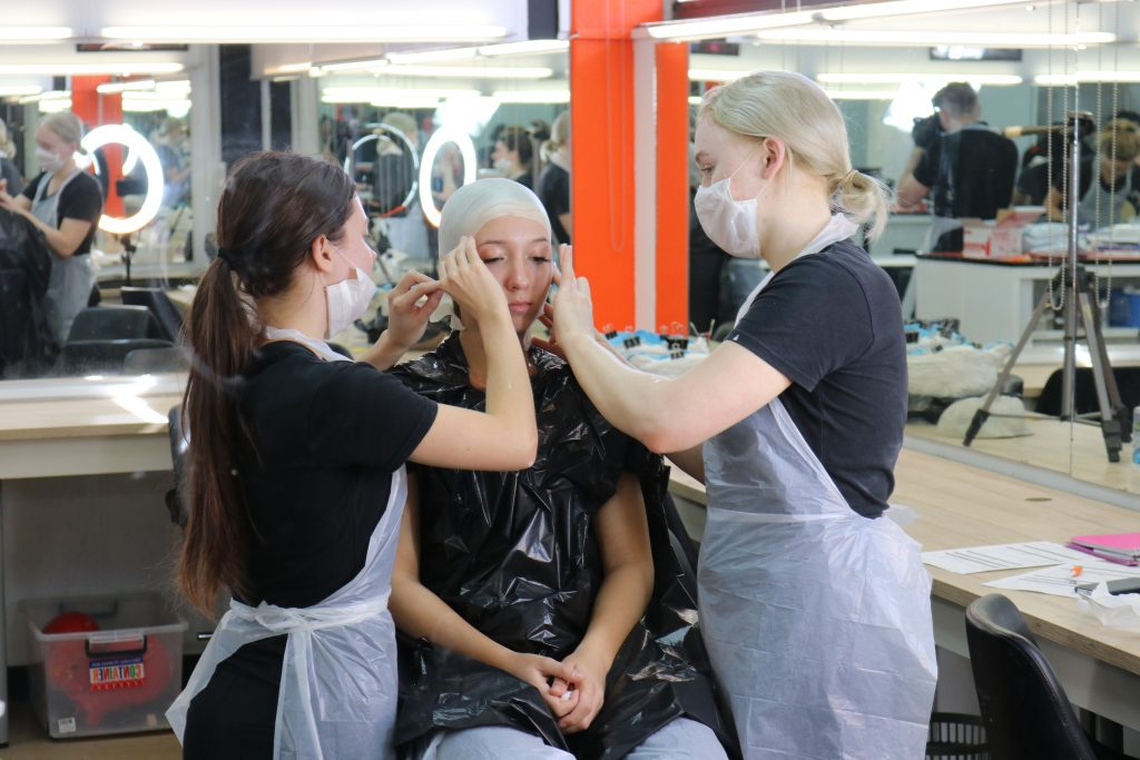 Gemma and Leonie applying bald cap to Georgia