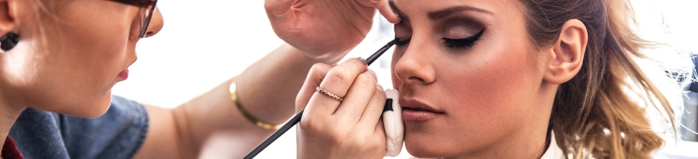 Woman having Eyeliner applied by makeup artist ACSM